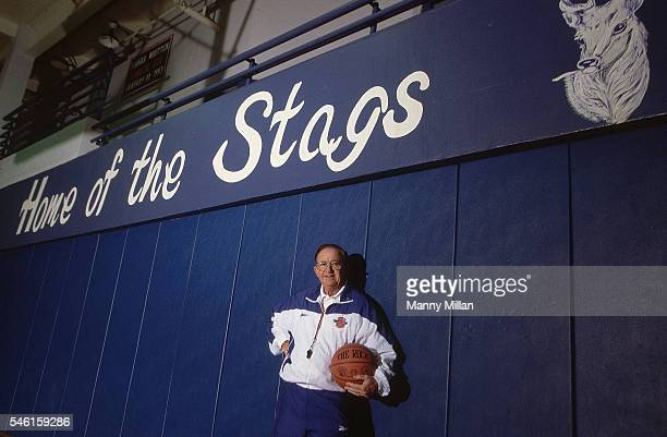 DeMatha HS coach Morgan WoottenWootten below sign on wall reading HOME OF THE STAGS during photo shoot in gym Hyattsville MD CREDIT Manny Millan