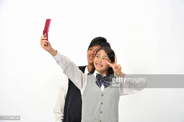 High School Boy and Girl Taking Photograph by Cellular Phone