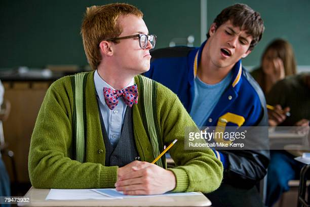 High school boy jock cheating off a high school nerd