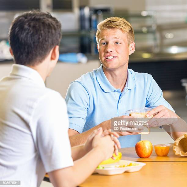High school boys eating healthy lunches together in cafeteria