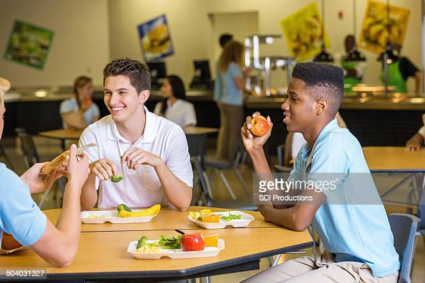 High school boys eating lunch together in cafeteria lunchroom