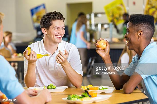 High school boys laughing together while eating lunch in cafeteria
