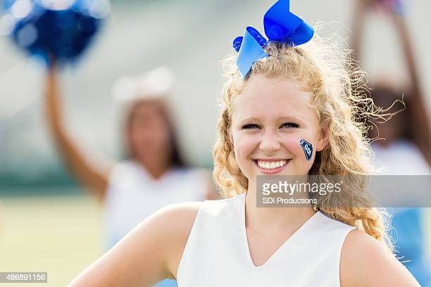 High school cheerleader smiling during football game or cheer event