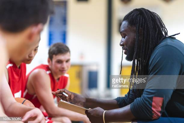 high school coach gives his basketball players a pep talk - pep talk stock pictures, royalty-free photos & images