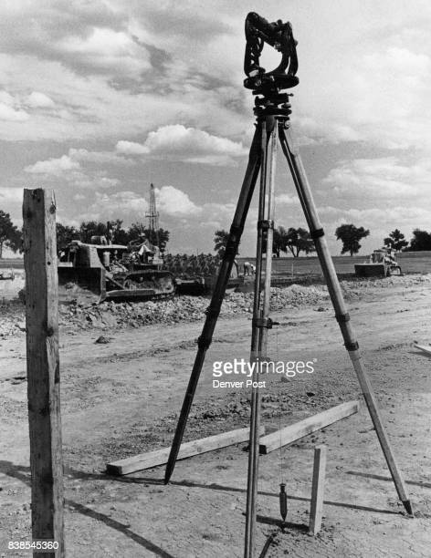 Early View Appearance of these geometrical shapes — a surveyor's transit in foreground a well driller's rig in background and earthmoving equipment...