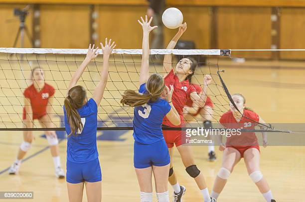 high school female volleyball player spiking the ball - volleyball mannschaftssport stock-fotos und bilder