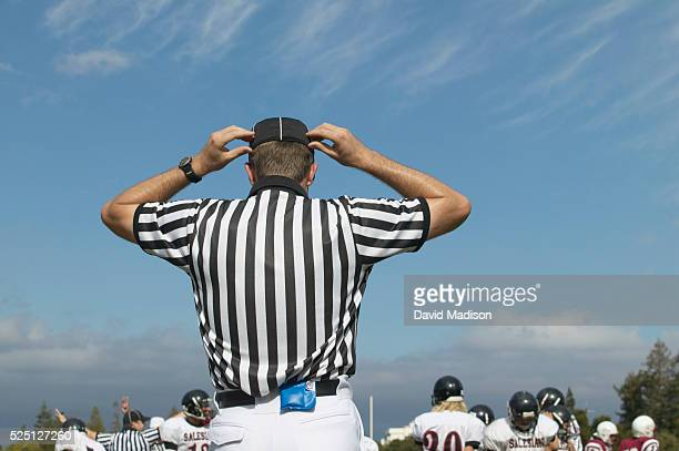 High school football referee adjusts his cap during a game between Sacred Heart Prep of Atherton, California, and Salesian High School of Richmond,...