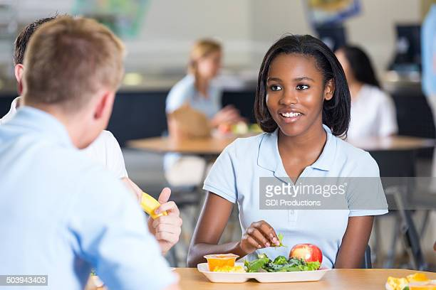 High school girl eating healthy food in cafeteria with friends