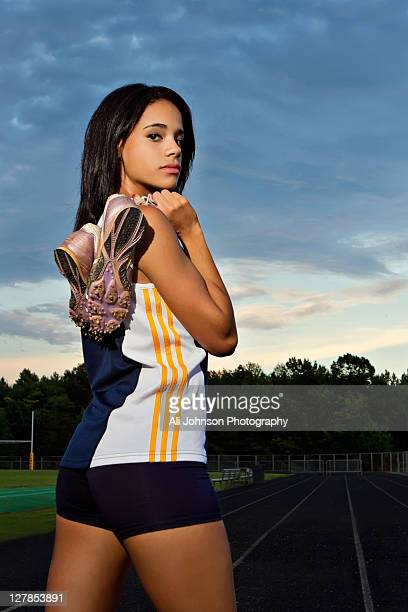 high school girl holding track cleats. - cleats stock pictures, royalty-free photos & images