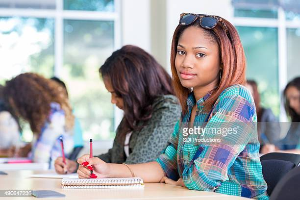High school girl looking up while taking exam in classroom