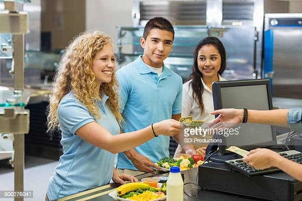 High school girl paying for lunch with cash