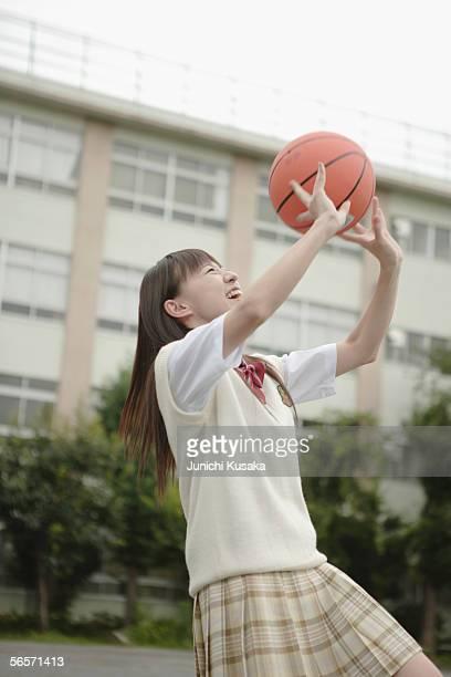 High school girl playing basketball in schoolyard