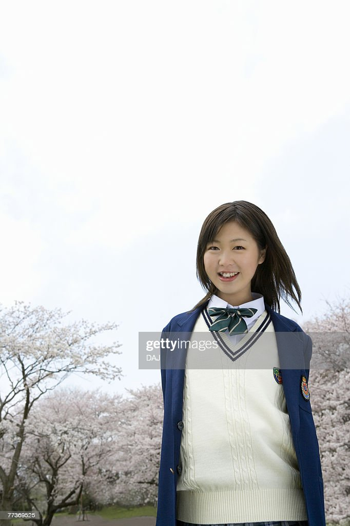 High School Girl Smiling and Looking at Camera, Cherry Blossoms in the Background : Photo
