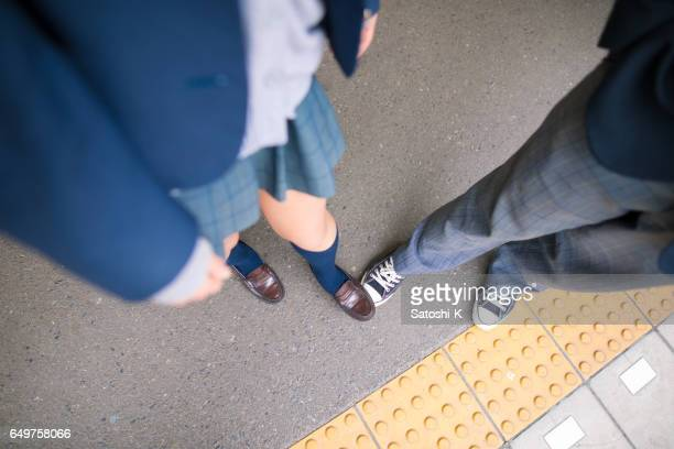High school girl stepping  on the boy's foot
