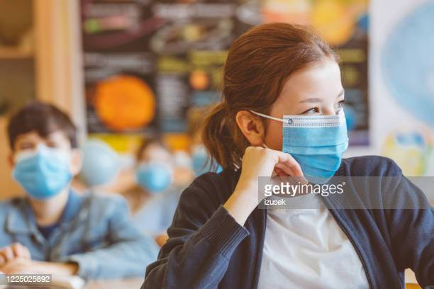 high school girl student at school wearing n95 face masks not listening - izusek stock pictures, royalty-free photos & images
