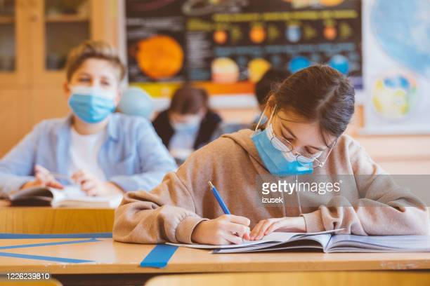 high school girl student at school wearing n95 face masks - classroom stock pictures, royalty-free photos & images