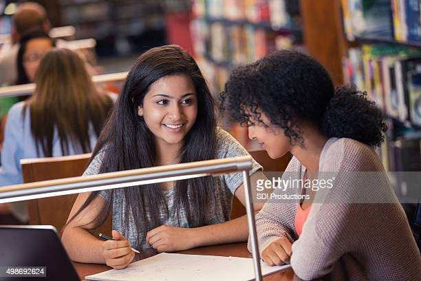 High school girl studying for exam in library together