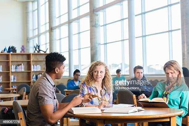 High school girl studying with tutor while mom reads nearby
