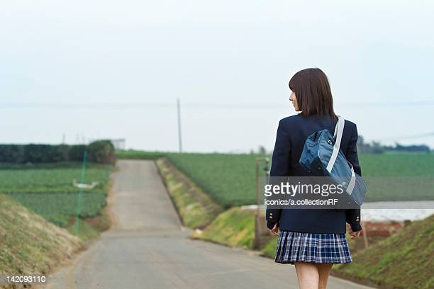 High school girl walking on rural road