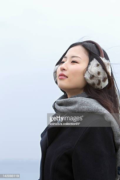 high school girl with ear muffs - 防寒着 ストックフォトと画像