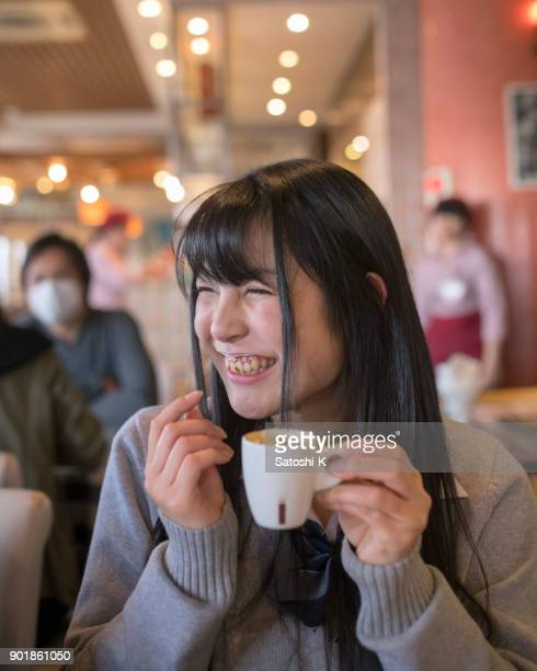 High school girl with milk mustache in cafe