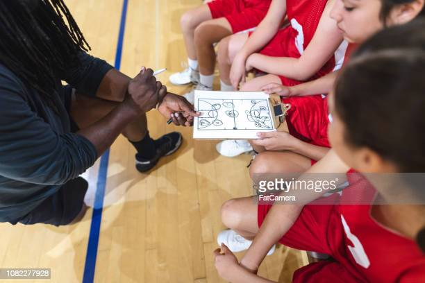 high school girls basketball coach gives his players a pep talk - basketball team stock pictures, royalty-free photos & images
