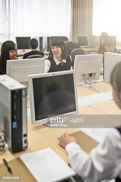 High school girls discussing in computer lab