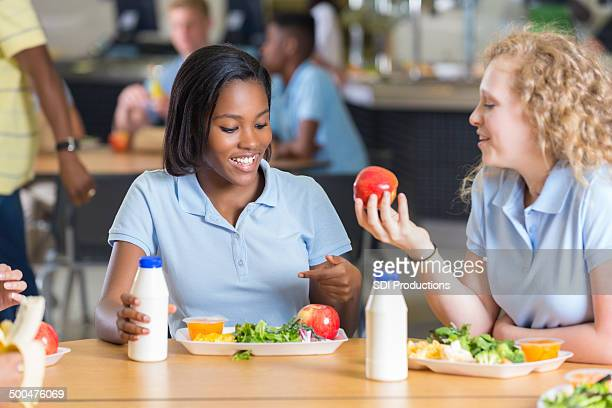 High school girls eating lunch together in lunchroom