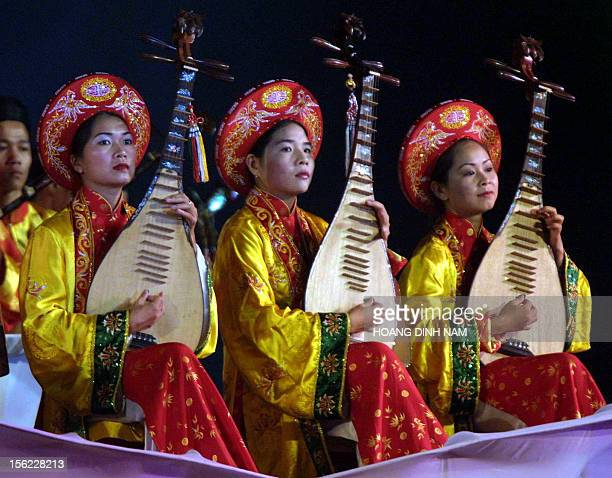 High school girls in traditional 'ao dai' dress and carrying conical hats walk on Trang Tien bridge during a fashion show held late 08 May 2002 in...
