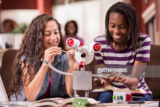 High school girls work on robot for education, engineering science project.