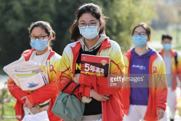 High school grade three students wearing face masks arrive at school after the term opening was delayed due to the COVID-19 coronavirus outbreak, in...