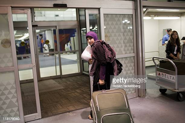High school graduate Asmaa Rimawi carries her suitcases at JFK Airport August 26, 2010 in Queens, New York to catch a flight to Boston, Massachusetts...