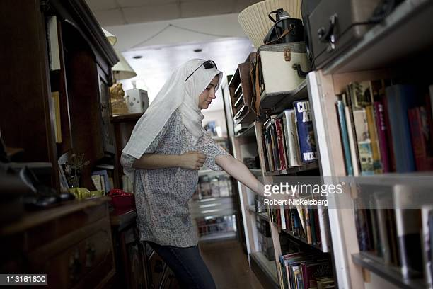 High school graduate Dania Darwish, 17 years, browses for books at a neighborhood thrift shop July 9, 2010 in Brooklyn, New York. She graduated in...