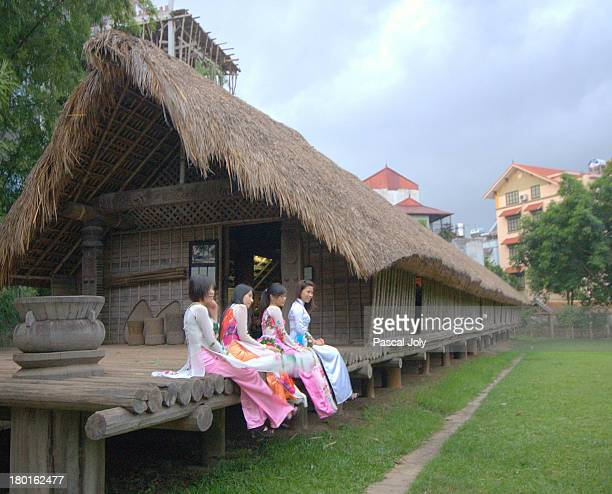 High School graduates dress up for picture in front of a long house from a remote hill tribe. Hanoi Museum of Ethnography.