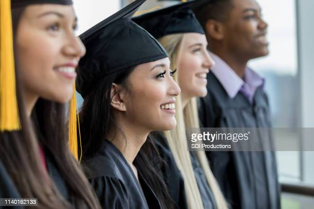 high school graduates in a row - black hat stock pictures, royalty-free photos & images