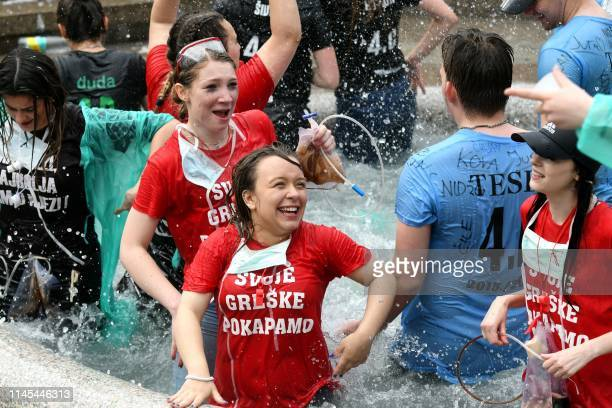 High school graduates take a bath in a fountain as they celebrate in central Zagreb on May 22, 2019. - Tens of thousands of graduates traditionally...