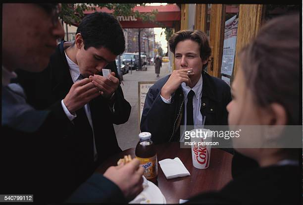 High school kids eating lunch and smoking outside Mimi's Pizzeria in Manhattan