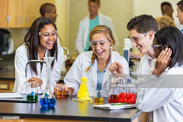 High school lab partners doing chemistry experiment in science class