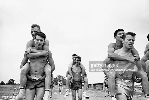 High school males in a particularly rigorous physical education class carry each other on their backs around the running track May 1958 Carmichael...