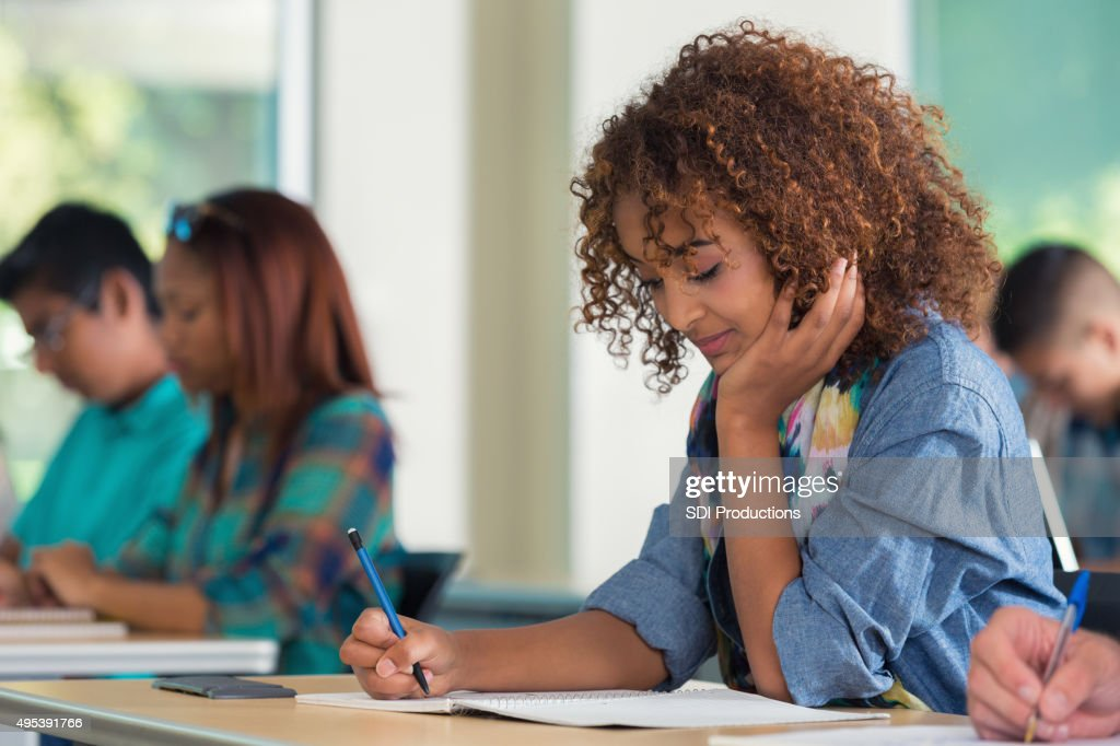 High school or college girl taking exam in classroom : Stock Photo