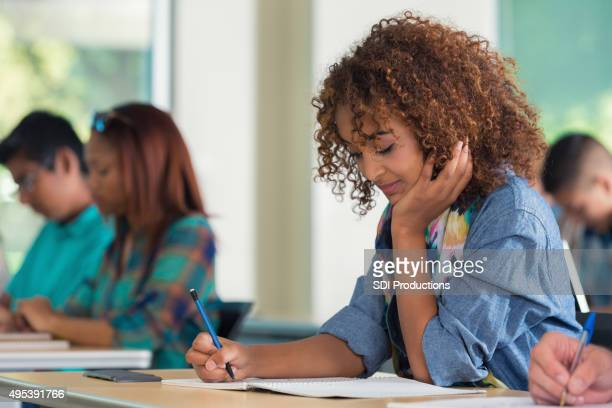 High school or college girl taking exam in classroom