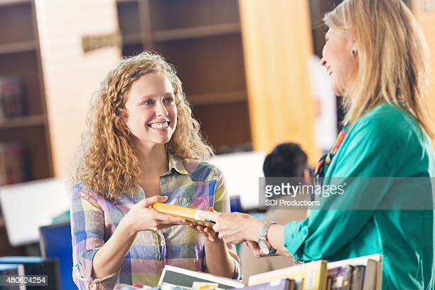 High school or college student checking out book in library
