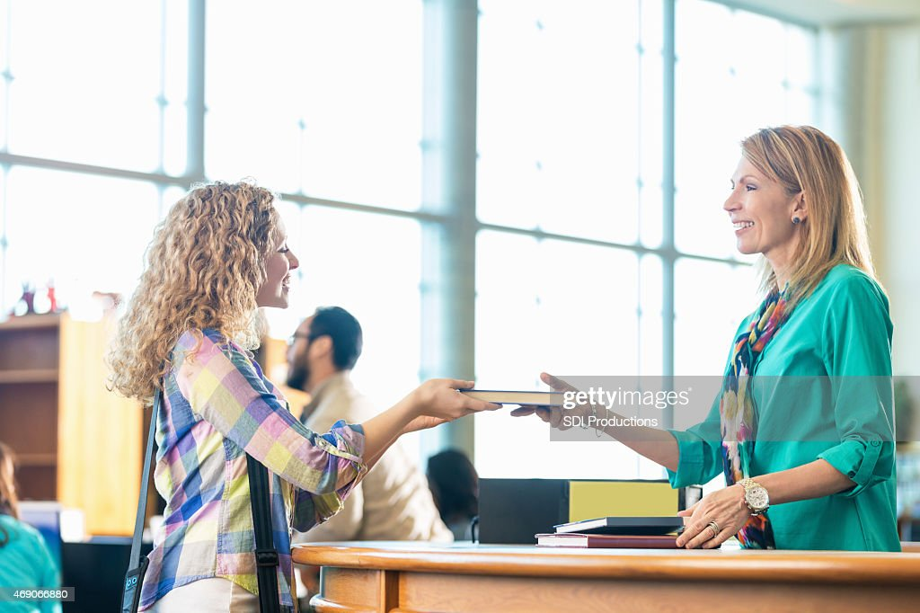 High school or college student returing library book : Stock Photo