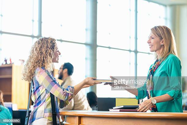 high school or college student returing library book - returning stock photos and pictures
