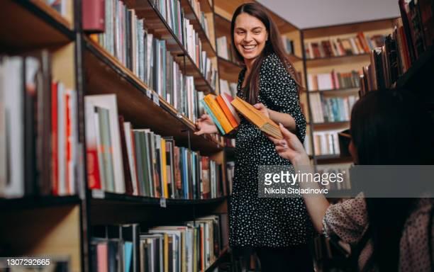 biblioteca de reajuste de estudiantes de secundaria o universitario - devolución del saque fotografías e imágenes de stock
