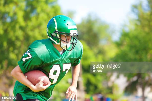 high school  or university american football player playing in field - american football uniform stock pictures, royalty-free photos & images