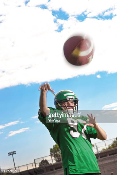 high school  or university american football player playing in field - quarterback stock photos and pictures