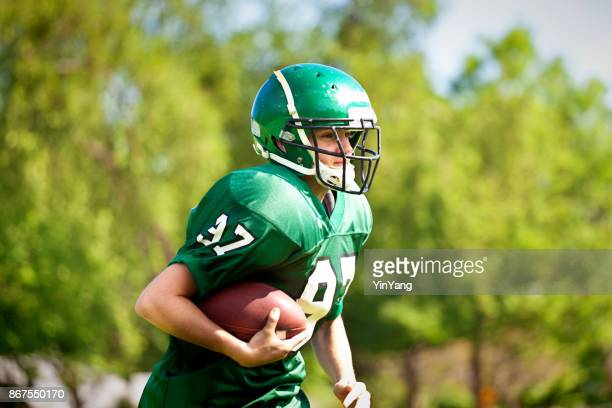 high school  or university american football player playing in field - high school football stock pictures, royalty-free photos & images
