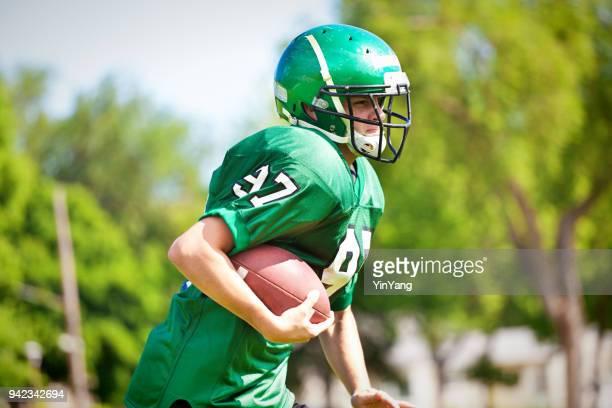 middelbare school of universiteit american football-speler afspelen op gebied - football league stockfoto's en -beelden