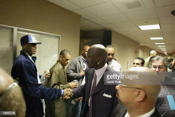 High school phenomenon LeBron James of the St. Vincent-St. Mary Fighting Irish shakes hands with Michael Jordan of the Washington Wizards after...